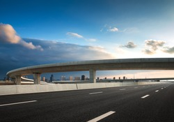 The clear sky in the evening, the curved approach bridge of the highway overpass leading to the city