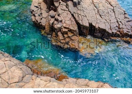 The clear turquoise sea water of Green Bay, Meru Betiri National Park, Banyuwangi, East Java, Indonesia, with rocks on the shore 商業照片 ©