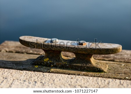 The cleat mounted on the shore of the jetty on the lake. A place where boats and yachts moor on jetties. Season of the spring. #1071227147
