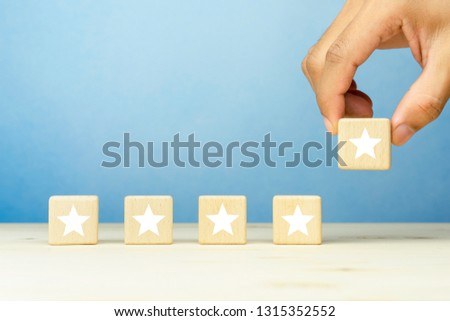 The client's hand put wooden blocks with a five star symbol, evaluation, Increase rating, Customer experience, satisfaction and best excellent services rating concepts. copy space #1315352552