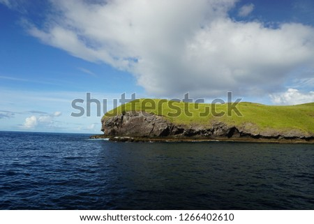 The cliff at the edge of the island covered by green grass field, the blue sky with clouds and blue sea as the background. #1266402610