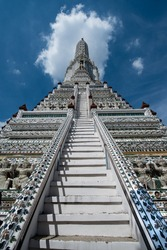 The climb of the white decorated tower in Bangkok and its steep stairs and a blue sky