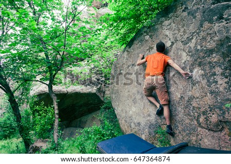 The climber climbs the stone. The athlete is engaged in bouldering. Rock climbing in nature.