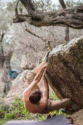 The climber climbs the stone. The athlete is engaged in bouldering. Rock climbing in nature. the concept of bouldering as a type of rock climbing and outdoor activities.