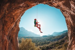 The climber hangs on a rope against the backdrop of beautiful mountains. The girl goes down. Rock climbing in Turkey. Mountain landscape. Exercise in the fresh air. Rock in the form of an arch. Cave.
