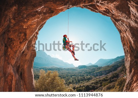 The climber hangs on a rope against the backdrop of beautiful mountains. The girl goes down. Rock climbing in Turkey. Mountain landscape. Exercise in the fresh air. Rock in the form of an arch. Cave. #1113944876