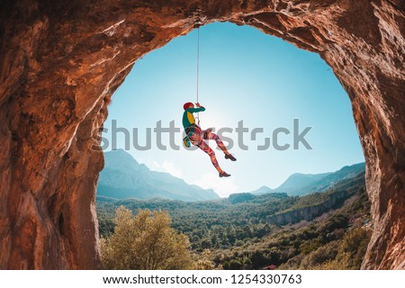 The climber is hanging on a rope. The girl goes down. Rock climbing in Turkey. Mountain landscape. A woman is engaged in extreme sports. Rock in the form of an arch. Climbing route in the cave.