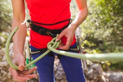 The climber is tying a knot on the safety system, Knot made of climbing rope, Safety in extreme sports, Climbing equipment for belaying, The girl is preparing to climb the route.