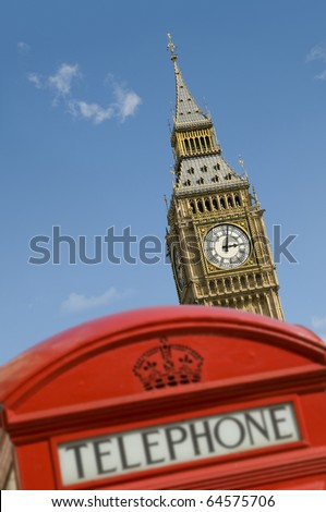The clock tower of the Palace of Westminster in London, UK behind a classic red telephone box. It is commonly referred to as Big Ben although this is the nickname for the great bell.