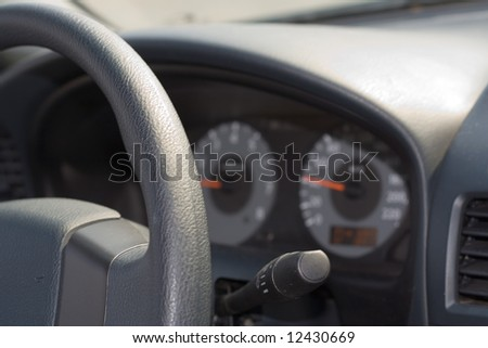 the close-up interior view of moving passenger car wheel and dashboard