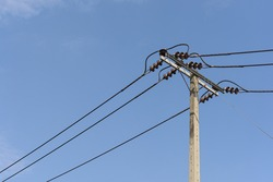 The close up of electricity power cable on concrete pole on sunny day with bright clear blue sky as a background