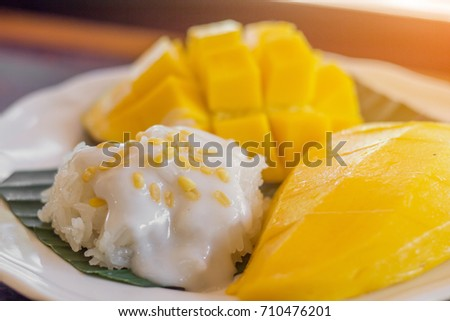 The close up of sticky rice and heap yellow mango by restaurant style setting in the dish with the green banana leaf under in the natural light.
