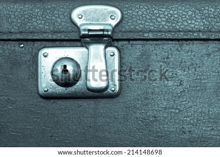 the closed metal rusty lock closeup on part of an old suitcase with the textured leather surface of dark blue color