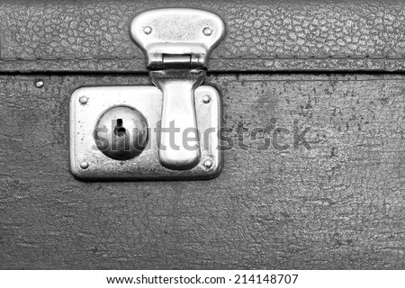 the closed metal rusty lock closeup on part of an old suitcase with the textured leather surface of dark gray color