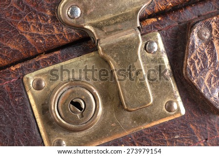 the closed metal rusty lock closeup on part of an old suitcase with the textured leather surface of dark brown color