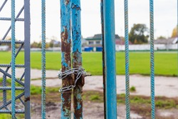 The closed old shabby gates of the stadium, wrapped in a chain during the lockdown period in connection with the COVID-19 pandemic, the coronavirus infection. Background
