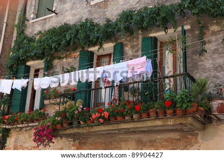 The clothes and bed-clothes is dried on a balcony. Venice cityscape, Italy