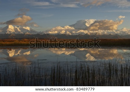 The 20320' cloud enshrouded Mt. McKinley and a portion of the Alaska Range reflect into a kettle hole pond as evening settles on Denali National Park, Alaska.