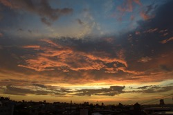 The cloud which burns with sunset in red and the silhouette of the city