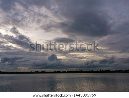 The clouds cover the sky, obscuring the light from the sun at sunset. The skyline divides the pond and the sky is covered with trees.