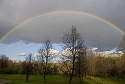 The cloudy sky and autumn rainbow above forest.