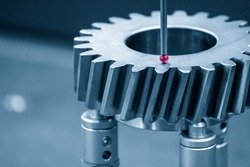 The  CMM machine checking the dimension  the bevel gear part . The quality control of mechanical parts with multi axis CMM machine.