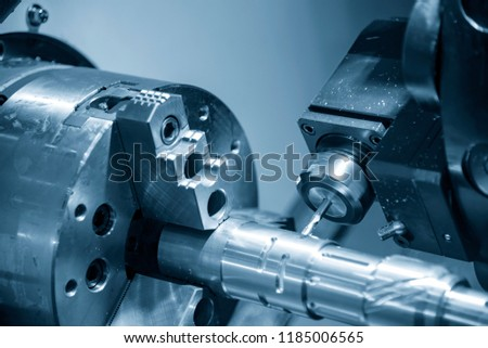 The CNC lathe machine cutting  the groove slot at the steel shaft by milling spindle .Hi-technology automotive part manufacturing process.