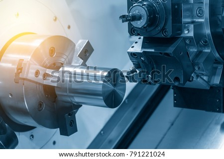 The  CNC lathe machine cutting the steel rod .The raw material bar clmaping on the CNC lathe machine