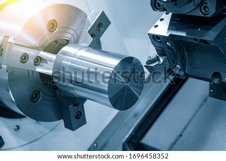 The CNC lathe machine rough cutting the metal shaft parts with lighting effect. The hi-technology metal working processing by CNC turning machine . Foto stock ©