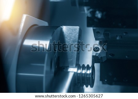 The CNC lathe or turning machine cutting  the slot  at the metal part.Hi-technology manufacturing process.