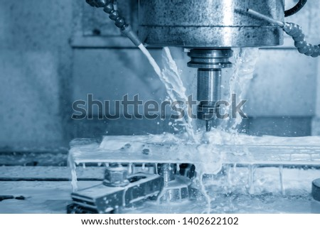 The CNC milling machine cutting the mould parts with ball end-mill tool. The liquid coolant method in CNC milling process.