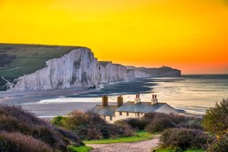 The Coast Guard Cottages and Seven Sisters Chalk Cliffs at sunrise in Sussex, England, UK