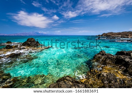 The coast of Chrissy island on a sunny summer day with turquoise sea water, a rocky bottom, yellow sand, black stones in the foreground and a blue clear sky with haze. Crete, Greece.