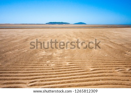 The coastal strip (coastline, beach) at low tide. A wide strip of desert sand to the horizon, a desert area, a wavy relief runs along it. An island is in the centre. Maсkey, Queensland, Australia.