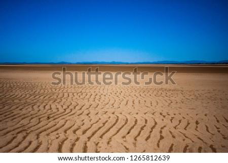 The coastal strip (coastline, beach) at low tide. A wide strip of desert sand to the horizon, a desert area, a wavy relief runs along it. Makey, Queensland, Australia.