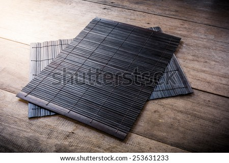The Coaster, Dark brown bamboo mat on wooden background