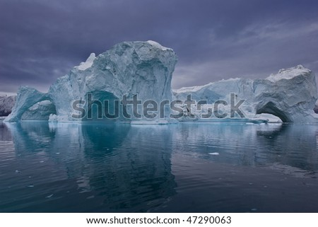 the coastline of east greenland with giant icebergs floating on the sea