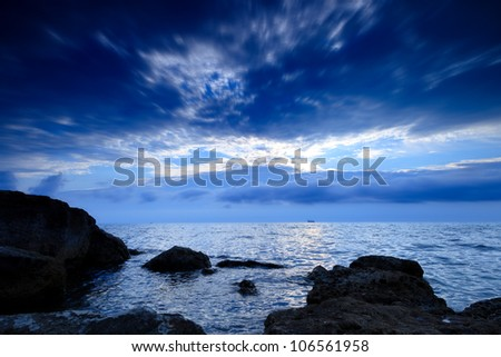 The coastline of the evening, the sea, rocks and the sky overcast