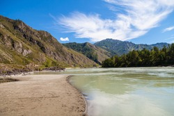 The coastline of the Katun River in Altai with a sandy beach on a summer day against the backdrop of mountains and blue sky.