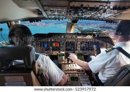 The cockpit of modern jet airplane. Aircraft flies above the city landscape and river. Pilots at work.  Сток-фото ©