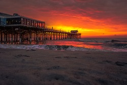 The Cocoa Beach Pier and the dramatic stormy sky with reflections and waves.