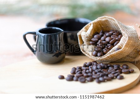 The coffee beans are in a sack beside the black ceramic glass on the wood table, focus on the coffee beans to make the background blur. #1151987462