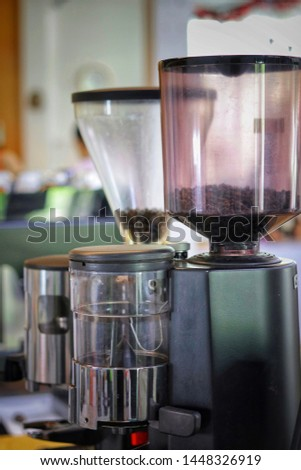 The coffee grinder machines fill with some coffee beans in the top tranparent buckets #1448326919