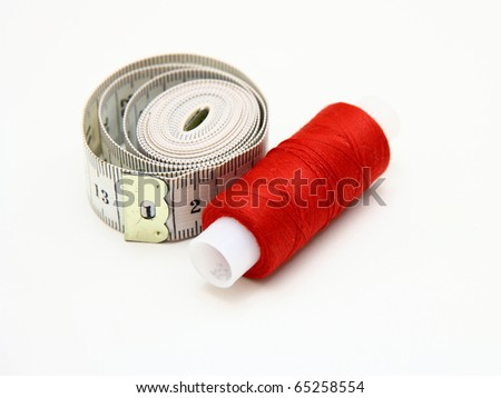 The coil of a red thread with centimeter on a white background