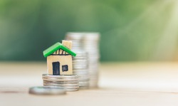 The coin is stacked vertically and has a wooden house green model placed on top coin, Saving money for real estate with buying a new home and loan for prepare in the future concept.