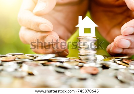 The coins are placed together and there is a small white paper house on top. As the two men's hands are encircled. #745870645