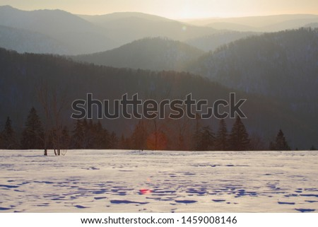 The cold early winter mountains are covered with snow and the trees are still standing. The sunrise sun shines on the snow and the forest, forming a beautiful and serene picture with the cascade of mo