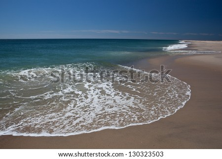 The cold north Atlantic ocean erodes the sand from the Cape Cod National Seashore in Massachusetts.  This sandy peninsula is easily affected by storms and wave action.