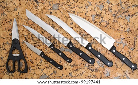 The collection of kitchen knives and scissors on the cork background