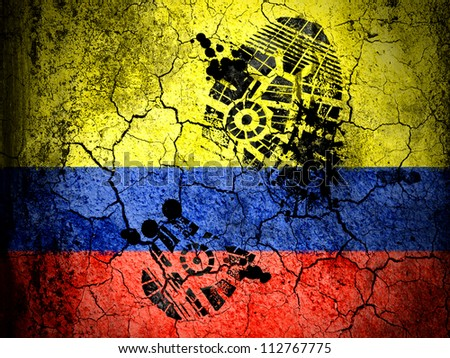 The Colombian flag painted on cracked ground with vignette with dirty oil footprint over it